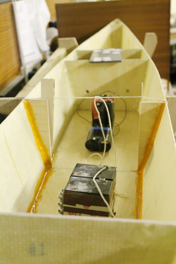 Next, we epoxied the deck down to the hull. We used batteries as weights to maintain contact between the deck and the hull as the epoxy cured.